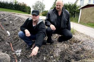 Från vänster Mikael Hamrin och Lars-Åke Öberg betraktar den avklippta kabeln som gör att de varit utan telefon i en vecka.