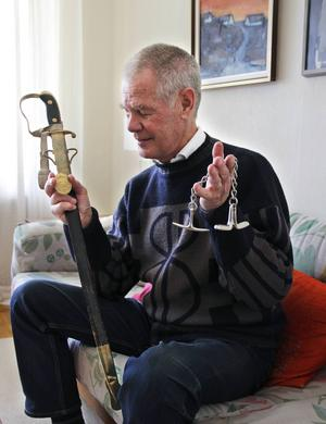 Kjell Hagman visar upp sabeln och handfängslet som han hade som utrustning när han började jobba som polis för 50 år sedan.
