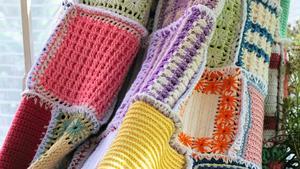 Grytlappar i milda pastellfärger, köpta på loppis, virkades ihop till remsor. Remsorna fästes ihop med säkerhetsnålar och virkades ihop. Slutligen syddes en kastsöm runt hela rektangeln – och vips, en originell filt!