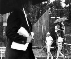 Vanlig syn. Regn över SM-tennisen på Fridnäs. VTK:s mästarpar i dubbel, Leif och Kjell Johansson, funderar över fortsättningen. Liksom tävlingsledaren Erich Aas, närmast. Paraplyförsedd domare skriver ned siffrorna.