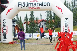 Två glada löpare tar sig i mål