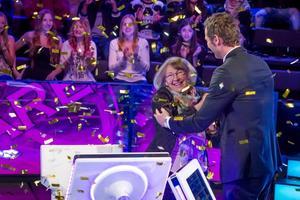 Birgitta Hedström från Sundsvall gratuleras av programledaren Rickard Sjöberg efter att ha vunnit en miljon i Postkodmiljonären.
