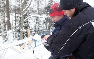 Andreas Hult och Göran Ivars läser sig till hur byggnadsställningen ska monteras ihop.