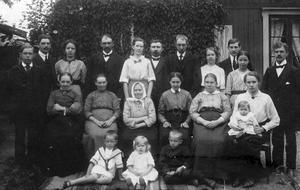 På det här gamla fotografiet syns Per Johan Axels änka (med schalett), Carolina Andersdotter, 1845-1922. Hon fick nio döttrar och en son (Per Axel Ambrosius, stående som nummer två från vänster).