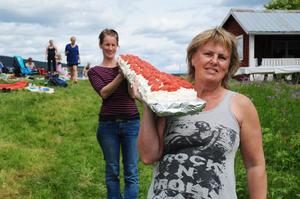 Ulrika och Ulla bär ner den långa tårtan.