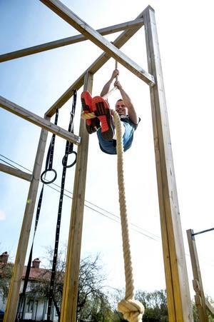 Repet som hänger ner från en över fyra meter hög träställning lockar till klättring.