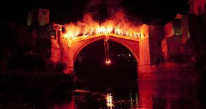 Upplyst bro och simhoppare med facklor på kvällen.