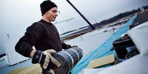 Arbete vid byggmästers stora bygge på Hacksta angående att det är lättare att arbete när det är mild vinter. Företaget Svetak:s Alexander Höök bär takpapp på det 6000 kvm stora taket.
