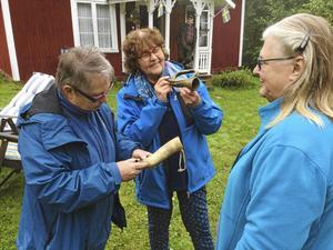 Birgit Lundgren, ordförande i Trönö hembygdsförening, t.v. var mycket intresserad av det s.k. tjuthornet från 1810. Barbro Berger, provar jägarhornet och Eva Eriksson tittar på.