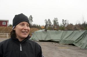 Anna Boman står framför delar av det ridhus som ligger nedmonterat i Tälje.  Där hoppas Söderhamns Hästsportklubb att drömmen om ett eget ridhus ska blir veklighet.