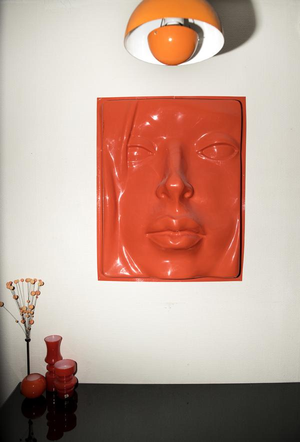 I hallen hänger Verner PantonsFlowerpot lamp, och på väggen hänger ett tredimensionellt verk i plast. Glasvaserna på bänken kommer från Lindshammar.
