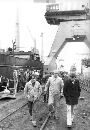 1980. De strejkande hamnarbetarna vägrade att ge upp. Här lämnar fr.v. Jan Thunberg och Arthur Lindén från Paltrans Shipping AB kajen efter att polismästare Hans Högberg (i svart rock) förgäves försökt övertala de strejkande att lämna plats åt hamnkranen.