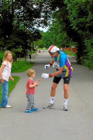 Kalle Svärd bistår med vatten till Janne Paraniak, Huddinge, som sprang sitt 261:a maratonlopp.