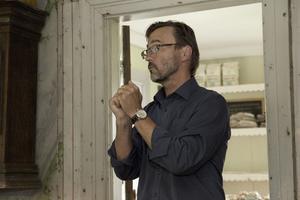 Björn förklarar att det är viktigt att måla flera lager, vilket är tidskrävande men ger det bästa resultatet.