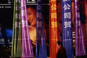 Mannen som passerar reklamen är munk. Bilden är tagen vid ett jättestort varuhus i Lhasa, största staden i Tibet.