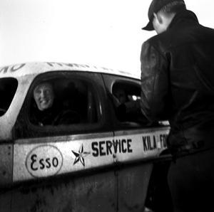 En funktionär kollar att föraren är regelrätt i ordning för start på ett heat i en Stock Car-tävling.