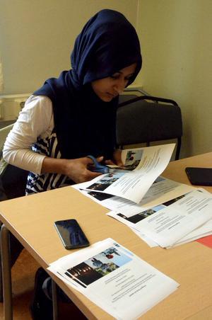 Söker fotouppdrag. Farah Al-ameeri klipper isär flyers som hon ska dela ut för att marknadsföra sig som fotograf.