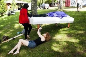 Sängplats i Ängsholn. Josefine Östberg Olsson (med skruvdragare) får lyfthjälp vid sitt konstverk som intar en central plats i parken.