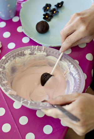 Kakdegen som fått stelna lite i frysen snurras varsamt i smält choklad innan den kan ätas.En ros växer fram när Sandra Eklund spritsar frostingen på cupcakes.