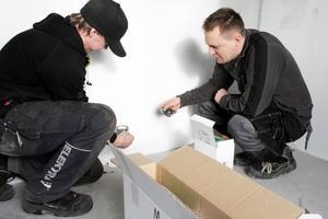 Olov Wängborg och Thomas Eriksson jobbar med att installera datauttag i ett av sovrummen i fyrarummaren.