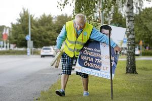 Lennart Karlsson i färd med att montera affischer på vägen ut mot Adolfsberg, ett av Moderaternas starka fästen.