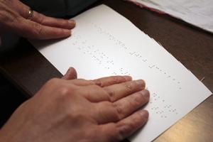 Blindskrift. Maria är blind och får läsa med fingrarna.