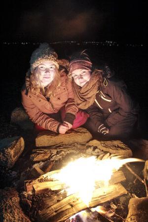 Fältbiologerna Miloo Demår och Maja Lindvall bjuder in andra ungdomar att göra dem sällskap vid lägerelden.