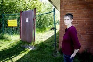 """OROLIG MAMMA. Det var genom den här glipan som sexåringarna tog sig in på badet som lades ned för några år sedan och sedan vidare ut till ån, """"spökskogen"""" och järnvägen på andra sidan området. Även förra veckan tog sig sexåriga barn in här. Jeanette Nordin vill att badet antingen rivs eller att staketet lagas så att barnen inte kommer igenom."""