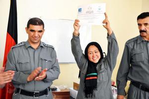 En afghansk kvinna visar stolt upp sitt bevis på att hon tagit polisexamen.