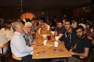 Svenskar och asylsökande Syrien delar måltidsgemenskap vid borden.
