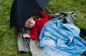 Hilda Ekholm tog en tupplur under firandet. Paraplyet skyddade mot vind och en och annan regndroppe som letade sig fram mellan solstrålarna - traditionellt midsommarväder alltså.
