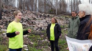 På bränd mark. Linn Suslin står mitt i skogen och berättar för besökarna om vad som händer med djurliv och växtlighet efter den stora branden förra året.