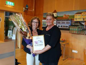 Lena Olsson, ägare av Eurosko i Ljusdal, tog emot pris från funktionshinderrådets ordförande Helena Brink (C).