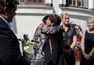 Carola Häggkvist kramar om Lotta Rudholms nära vänner vid begravningen i domkyrkan.