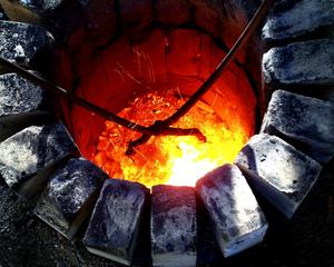 NU ÄR DET DAGS! Efter många timmars passning vid ugnen tas järnet upp med tång för att bearbetas och smidas.