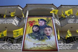 En av Hizbollahs martyrbilder hänger på ett hus i byn Harees i södra Libanon. På bilden syns tre släktingar, varav två dödades i kriget mot Israel 2006 och den tredje dödades i södra Aleppo i Syrien i juni i år.   Foto: Hassan Ammar/AP/TT