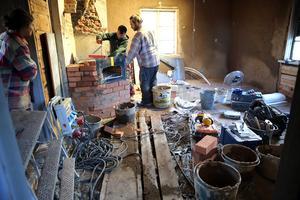 Dennis Lirbank och Darius Andrulevicius arbetar med lerarbete i en annan gård i Skattungbyn, Stess där Rebecka Dynesius och Andreas Marklund ska bo.
