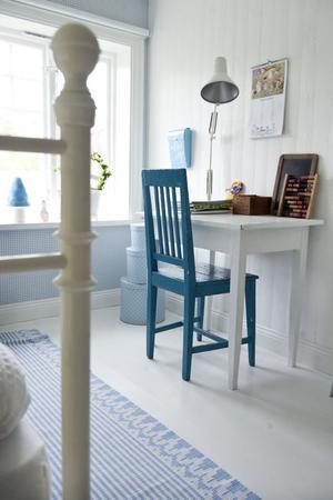 När man kommer upp för trappan till övervåningen tittar man rakt in i två mysiga barnrum under sluttande tak. Albins rum går i blått och vitt. Tapeten kommer från Sandbergs.