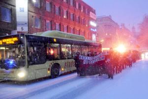 Mitt i trafiken drar tåget från Stortorget till Södermalmstorg. Ramsor mot fascism hös och bengaler tänds.