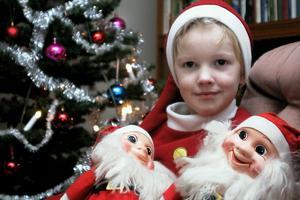 Barnbarnet Sebastian Jonsson kramar mamma Maries och morbror Tomas gamla jultomtar, som numera ingår i mormor Åsas samling och som står under julgranen.