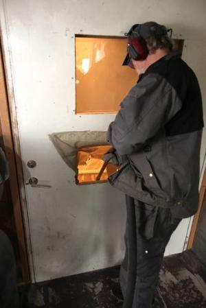 Genom ett hål i dörren blästrar Hassegravstenen tills den fått namn och årtal.