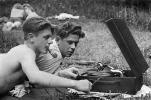 Två ungdomar spelar skivor på en resegrammofon ute i gröngräset på Långholmen i Stockholm sommaren 1944.
