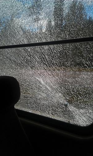 En 12-årig flicka hade platsen bredvid fönstret när skottet eller stenen träffade rutan. Som tur var låg hon ner på sätet i just det ögonblicket.