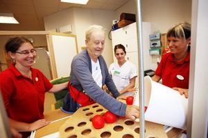 Sara Elasson, arbetsterapeut,  Sofie Croon, undersköterska och Ann-Christin Karlsson, arbetsterapeut hjälper Claes Ljung med sin träning, som går ut på flytta bollar från en hink till mindre hål.