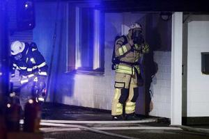 Rök och eld. Brandmän i rökdykarutrustning tog sig in i den brinnande byggnaden.