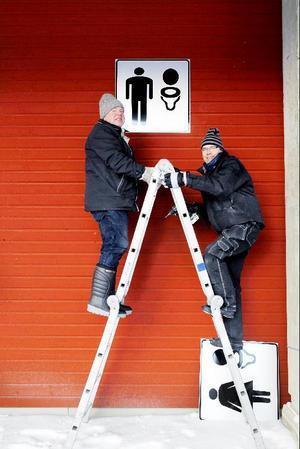 Julle Grönlund och Kurt Axelsson från skyltverkstan har hand om alla wc-skyltar och är i full gång med att fästa dem på rätt ställe.