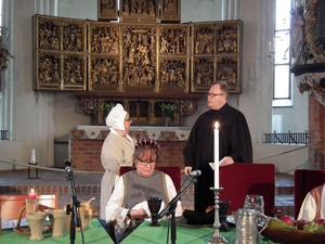Markus Holmberg är en given auktoritet i rollen som Martin Luther har en dialog med Elsmarie Ekström som spelar hans granne. Vid bordet sitter Christina Sandström som gestaltar Luthers fru Käthe.