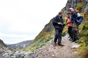 Möte på vandringsleden. Per Hjärpsgård, som vandrar i Dromskåran för första gången, möter en trio bestående av Sonja Sundqvist, Duved, Gun-Britt Albertsson, Hallen och Erling Granström, Järpen.Bydals- fjällen  i skimrande höstskrud.Det ges många tillfällen för fotografering längs leden.Ett valv av sten finns att skåda halvvägs genom Dromskåran.
