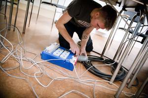 Teknikchefen Sune Berg preparerar strömanslutningen. Han har tagit på sig det fulla ansvaret för att lanet ska flyta rent tekniskt.