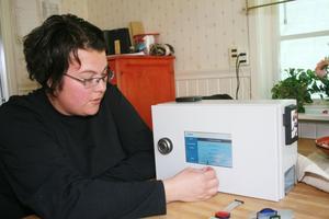 Linda Jansson testar sitt digitala skåp som laddas med medicindoser.